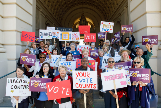 People standing on steps holding signs that say Women Power the vote, Vote and your vote counts.